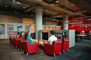 Students sitting around a fireplace at Koerner Library