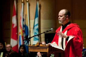 Douglas Coupland speaking at a podium at his honorary degree ceremony.
